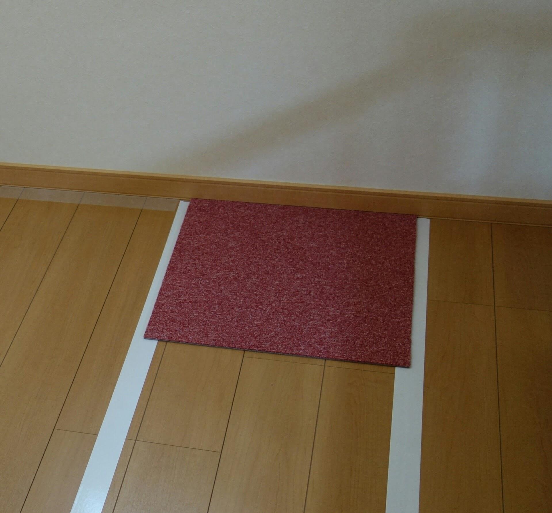 フローリングの床にタイルカーペットを貼る作業風景